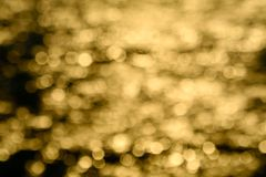 Gold color abstract of blur colorful light on sea water surface. Art, background, ball, beautiful, blurred, blurry, boat, bokeh, bright, dark, fishing, happy royalty free stock images