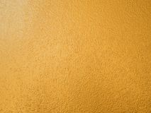 Gold color background. Rough gold texture design on the wall royalty free stock photo