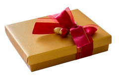 Gold color box with red ribbon in bow Stock Image