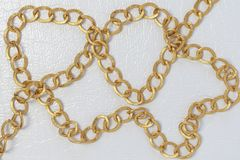 Gold color chain. Chain on white leather background royalty free stock photography