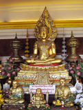 Gold-colored Buddha and monks statue in Buddhist temple Stock Photography