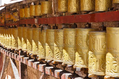 Gold colored Buddhist prayer wheels in Lhasa, Tibet. Gold colored Buddhist prayer wheels in the city center of Lhasa, Tibet Stock Photo