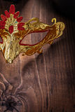 Gold colored carnaval mask on old wooden board very close up vie Royalty Free Stock Image