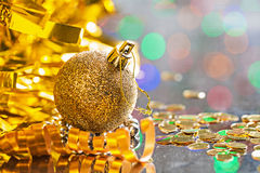 Gold colored christmas ball with string on background of bokeh h Stock Images