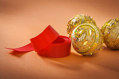 Gold colored christmas baubles and red ribbon on light brown bac Royalty Free Stock Image