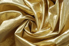 Gold Colored Fabric. Swirl of gold colored fabric background Royalty Free Stock Images