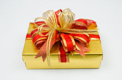 Gold colored gift box Stock Photos