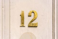 Number 12. Gold colored house number twelve 12 Royalty Free Stock Image