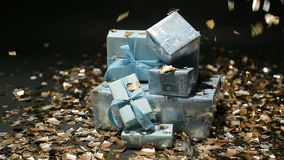 Gold confetti falling on blue gifts boxes. On black background stock video