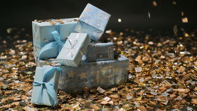 Gold confetti falling on blue gifts boxes. On black background stock footage
