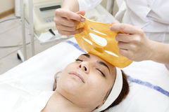 Gold cosmetic mask. Gold mask cosmetic procedure in the beauty salon Stock Photo