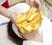 Gold cosmetic mask. Gold mask cosmetic procedure in the beauty salon Royalty Free Stock Photography