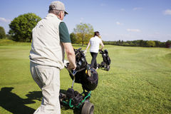 Gold couple walking on fairway with bags. Active senior golf couple pushing golf trolley with bag on fairway on beautiful golf course with blue sky in Royalty Free Stock Photography