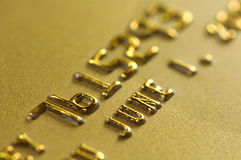 Gold Credit Card. Close-up of digits on a gold credit card. Very shallow depth of field. Focus on number 6. Visible texture of the card Stock Photography