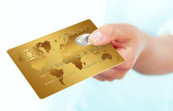 Gold credit card holded by hand over white. Background Stock Images