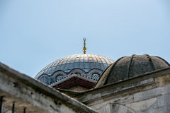 A gold crescent-topped finial hip-knob / alem on a mosque dome in Istanbul near Grand Bazaar with blue sky in the background. Stock Photography