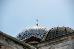A gold crescent-topped finial hip-knob / alem on a mosque dome in Istanbul near Grand Bazaar with blue sky in the background. Royalty Free Stock Images