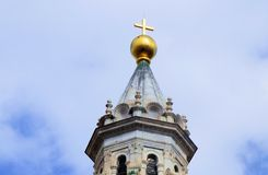 A gold cross atop a Bell tower shining in the sulight in Tuscany Italy. Gold cross atop bell tower shining sulight tuscany italy golden gleam catholic stock image