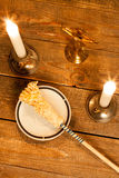 Gold cross with candles and  sprinkler on wooden background. Stock Photography