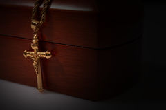gold cross and chain on a wooden box Stock Image