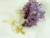 Gold cross and flower. Gold Christian Catholic cross lying on romantic white veil surrounded with beautiful flower lilac, romantic gold religious jewelry with stock photo