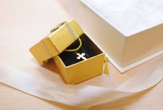 Gold cross in a gift box royalty free stock photos
