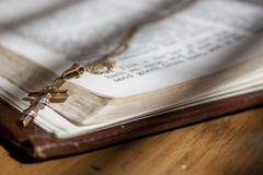Gold Cross on Holy Bible. A worn bible is showing the inside text and a gold cross is laying over the scripture stock photography