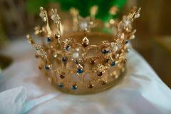 Gold crown with blue stones at the altar in the church for wedding couples traditional religious wedding ceremony. Gold crown with blue stones at the altar in Stock Photo