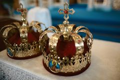 Gold crowns decorated with stones on the throne in the church for a wedding couple of the traditional religious wedding ceremony. Crowns decorated with stones on Royalty Free Stock Photography