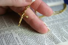 Gold Crucifix. Hand holding gold crucifix on open bible pages Royalty Free Stock Photography