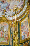 Gold crucifixion of Jesus Christ on a background of icons in the church of San Giovanni e Paolo in Rome, capital of Italy. Gold crucifixion of Jesus Christ on a royalty free stock image