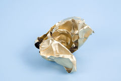 Gold crumpled paper. A ball of crumpled paper painted in gold. Minimal color still life and quirky photography stock images