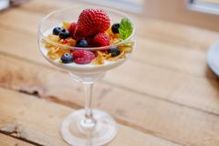 Crunchy corn flakes with some wild berries in a glass cup. Stock Photo
