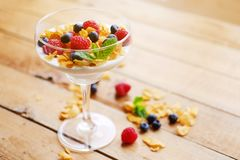 Crunchy corn flakes with some wild berries in a glass cup. Royalty Free Stock Images