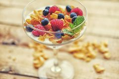 Crunchy corn flakes with some wild berries in a glass cup. Stock Images