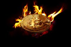Gold crypto currency coin - bitcoin in open fire. On a black background in open fire is a gold coin of a virtual digital crypto currency - bitcoin for business royalty free stock photos
