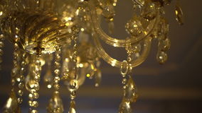 Gold crystal chandelier on a bright background. Slow motion stock video footage