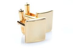 Gold cuff links on white background Stock Image