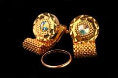 Gold Cufflinks. And wedding ring on black Stock Photos