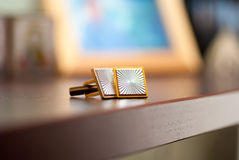 Gold cufflinks. Cufflinks lying on a wooden table Royalty Free Stock Image