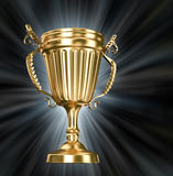 Gold cup on black background with blue rays Royalty Free Stock Photos