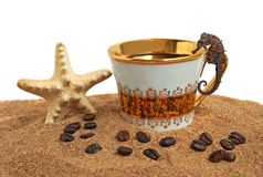 Gold cup with coffee. And beans on a sea beach stock image