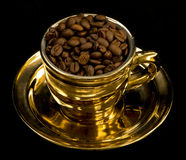Gold cup with coffee beans. On black background stock photos