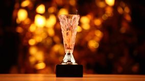 Gold cup fire flame wooden table gold bokeh hd footage. Studio stock video