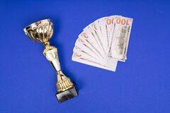 Gold Cup and money on blue background