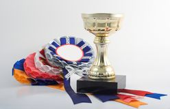 Gold cup with some ribbons awa Royalty Free Stock Photos