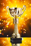 Gold cup trophy against shiny background Stock Image