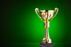 Gold cup trophy on green background Royalty Free Stock Photography