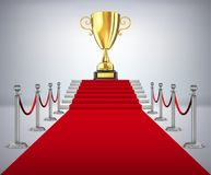 Gold cup of the winner on a red carpet path Royalty Free Stock Photo