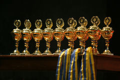 Gold cups. Stand on a table on a black background Royalty Free Stock Photos